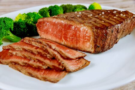 Sliced medium rare beef sirloin with broccoli on white plate.