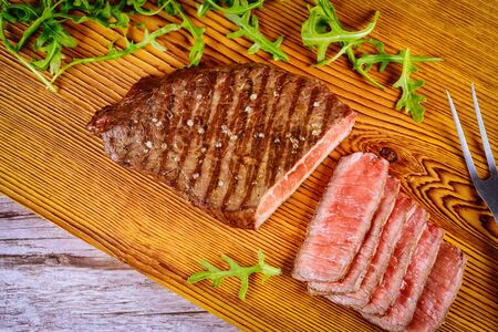Delicious and healthy grilled medium rare beef steak on wooden board with fork.
