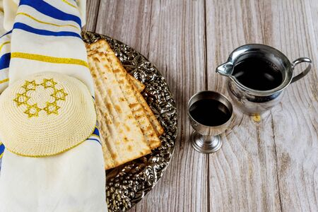 Matza, wine, tallit and kippa on wooden background. Jewish holiday concept.