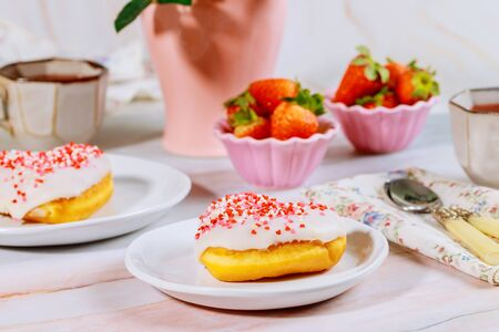 Breakfast with sweet sprinkle donut on white plate, strawberry and cup of coffee.