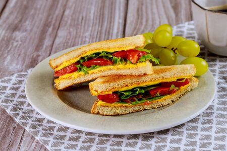 Toast with melted cheese, spinach, tomato and grape for breakfast.