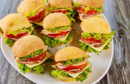 Delicious sandwiches made from ciabatta roll with ham, cheese, lettuce and tomato on white plate.