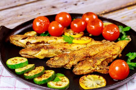 Fried small fish with tomato and lemon in a pan on a wooden background. Top view.