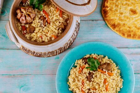 Uzbek pilaf with rice, meat, carrot and garlic in clay pot with flatbread. Stock fotó