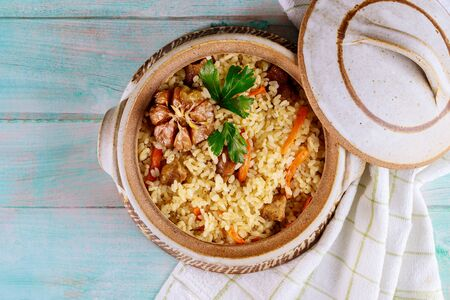 Rice pilaf with lamb, carrots, garlic and indian spices in clay pot with lid.