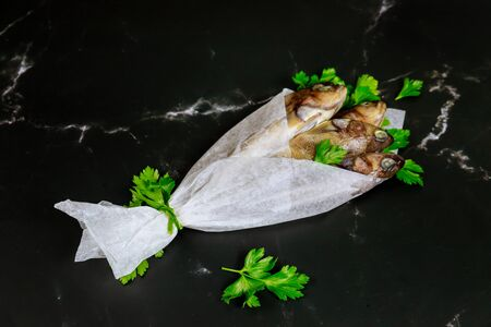 Fresh whole fish with parsley wrapped in parchment paper on black table. Top view.