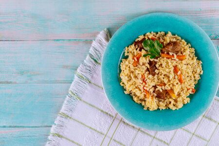 Thai rice with meat and vegetable in blue plate on wooden background. Stock fotó