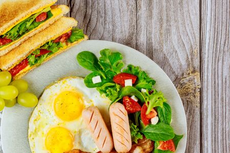 Pork franks, fried eggs, grilled cheese sandwiches and salad for breakfast.