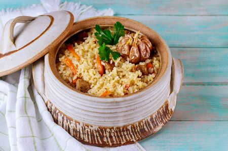 Uzbek pilaf with vegetable and meat in pot with lid on wooden background.
