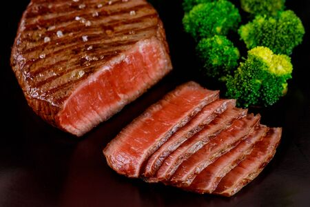 Sliced rare beef tenderloin with broccoli on black background on wooden table.