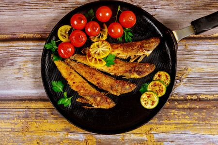 Fried whole capelin fish in a pan on a wooden background. Top view.