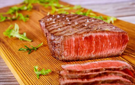 Grilled sliced rare angus beef steak on wooden board. Close up.