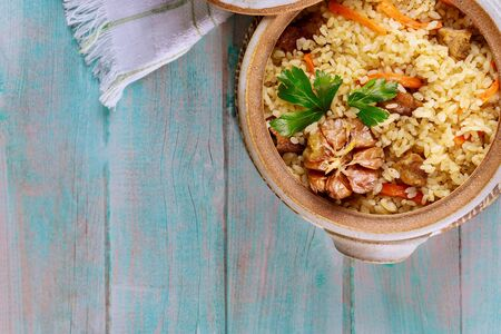 Chinese rice with vegetable and meat in clay pot on wooden background.