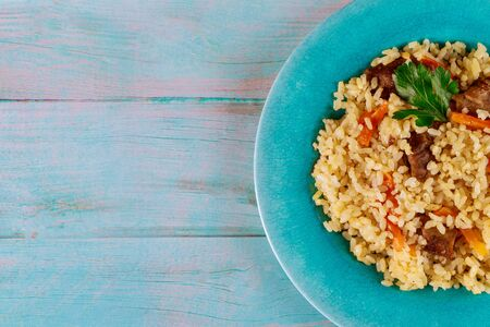 Fried rice with vegetables and chicken on plate and blue background. Chinese cuisine.