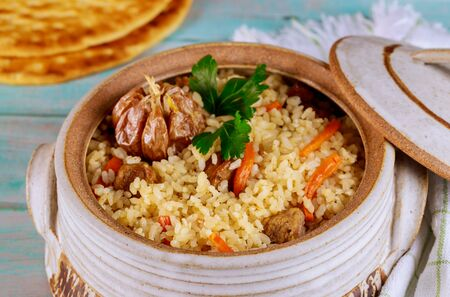 Turkish rice with vegetable and meat in pot with lid and flatbread on wooden background.