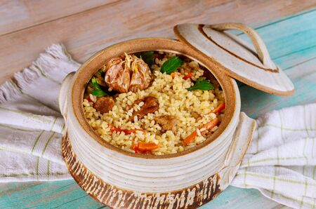 Rice with beef and vegetables in a clay pot with lid. Close up. Asian cuisine. Stock fotó