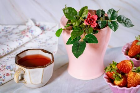 Fresh carkade tea with strawberry and vase with rose. Breakfast table.