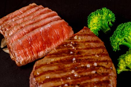 Juicy cooked rare beef sirloin with broccoli on black background.