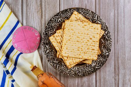 Matza, tallit and kosher wine in bottle on wooden background. Jewish holiday concept. Stock fotó