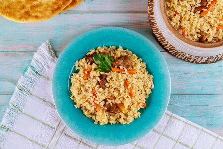 Asian rice with vegetable and meat in blue plate on wooden background.
