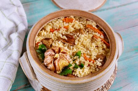 Spicy mexican rice with beef and carrots in clay pot.