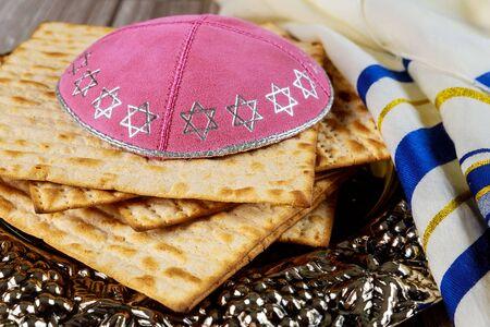 Matzo, tallit and kippa on silver plate. Jewish holiday concept.