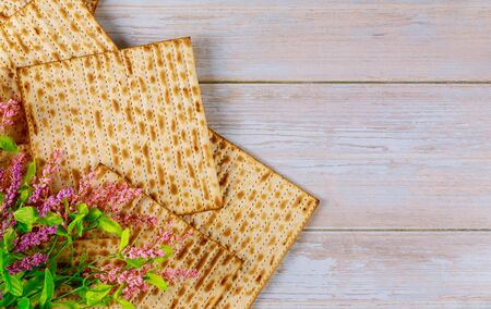 Jewish matzah bread with pink flowers on wooden rustic background. Passover holiday concept