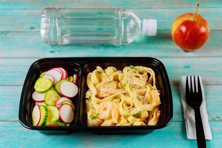 Ready meal on food container with fork, water and apple.