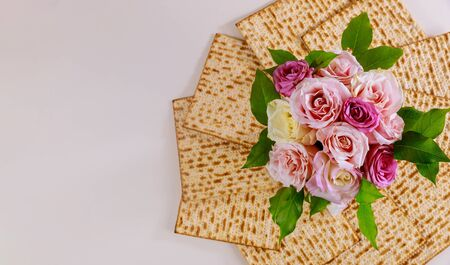 Jewish matzah bread with pink roses. Jewish Passover holiday concept.