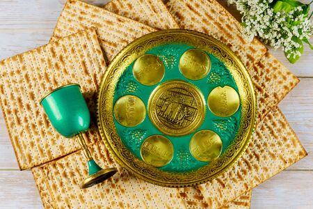 Jewish matzah, kiddush cup and seder with text in hebrew egg, bone, herbs, karpas, chazeret and charoset. Passover concept.