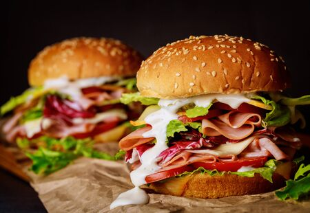 Sesame seeded sandwiches with ham, lettuce, cheese and tomato. Close up. Stock Photo