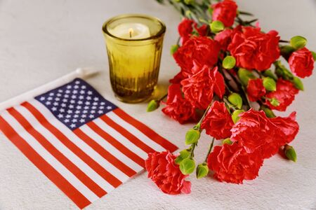 American flag and candle with red flowers carnation on white surface. Veterans Day.