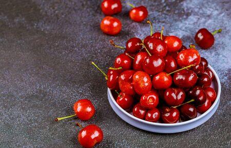 Fresh cherry with stem on plate on dark background.