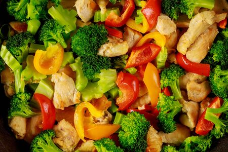 Healthy stir fry vegetables with chicken in pan on white wooden surface. Close up.