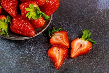 Beautiful sliced red strawberries on gray background.