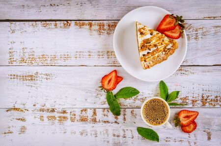 Piece of caramel pie with cup of coffee on white rustic wooden background. Banco de Imagens