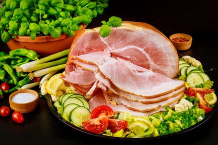 Pork ham with fresh parsley, dill and tomato on wooden rustic table. Stock Photo