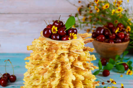 lithuanian spit cake sakotis decorated with fresh cherries.