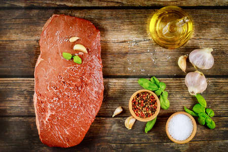 Raw beef meat on a wooden background with spice and oil. Top view.