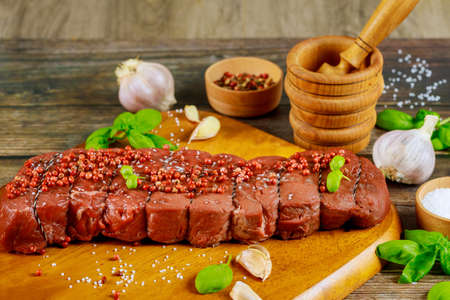 Raw beef fillet meat with herbs and spices on wooden board.
