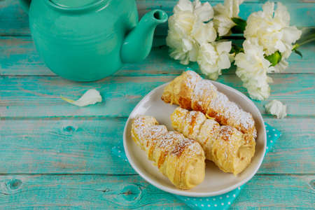 Crispy sweet rolls with whipped cream, teapot and flowers.