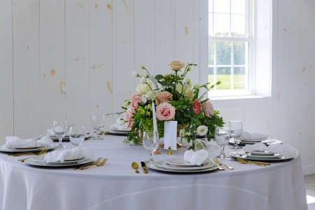 Elegance white table set with flower in restaurant.