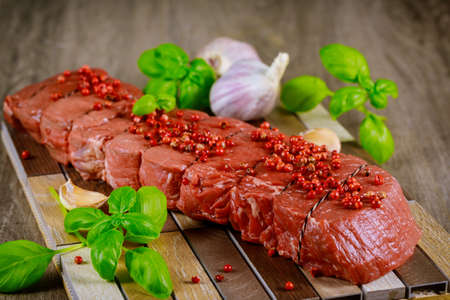 Raw rib eye beef steak with garlic and herbs on a wooden background.
