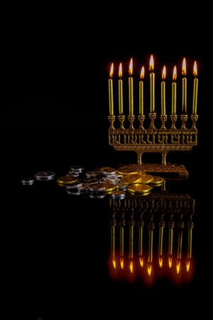 Menorah with golden burning candles, chocolate coins and reflection on surface for Hanukkah jewish holiday.