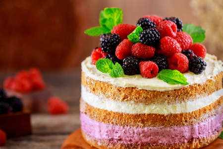 Delicious berry cake decorated with fresh raspberries and blackberries on wooden background.