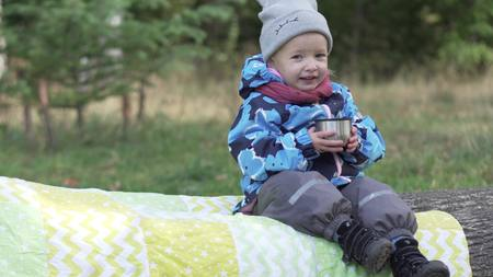 happy little girl drinks tea in the park. The baby is warmly dressed, it is autumn outside. A girl is holding a mug with warm drinks and smiling. Cute video Фото со стока