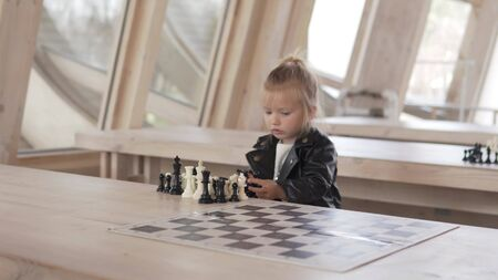 Beautiful little girl plays with chess pieces. She sits at a wooden table in a chess club and removes pieces from a game board. 스톡 콘텐츠