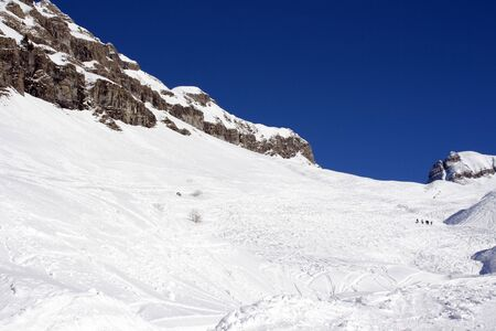 A picture of a snowy mountain side covered in ski tracks with a small group of skiers and a deep blue sky Stock Photo - 2646322