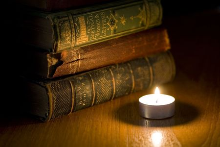 a pile of old books next to a small candle Stock Photo