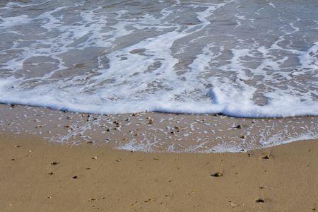 foamy: A foamy wave retreating from a beach Stock Photo